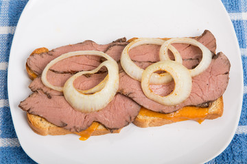 Rare Roast Beef and Sliced Onion Sandwich on White Plate