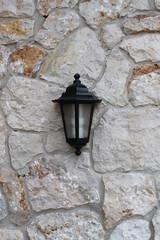 Lampe hängt an Steinmauer