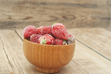 Frozen strawberries in a wooden bowl on wooden background
