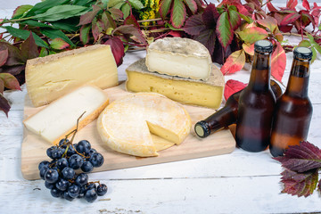 different French cheeses with a few bottles of beer