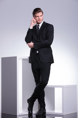 young business man leaning on a white modern furniture piece