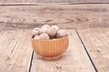 whole walnuts lying on faded wood with additional nuts in wooden
