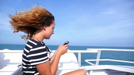 Woman Wearing Sea Sailor T-shirt on Yacht Using Cell Phone.