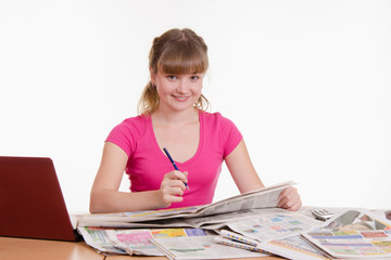 Girl looking in the newspaper classifieds