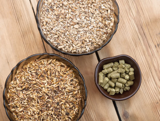 beer ingredients, hops and malt on wooden table top