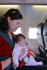 Mother carry her infant baby during flight