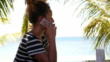 Young Woman Talking by Phone on a Beach.
