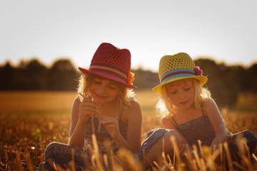 Two girls sitting in a cornfield