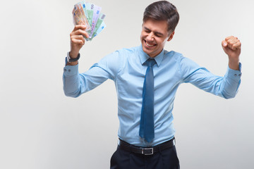Businessman celebrating money income against white background
