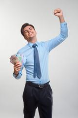 Businessman celebrating money income against white background