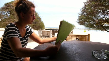 Woman Holds a Menu in the Beach Cafe. Slow Motion.