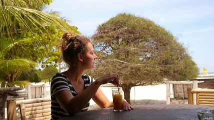 Woman Drinking Cocktail in Summer on Beach Bar.