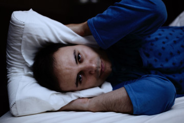 Man trying to sleep in his bed