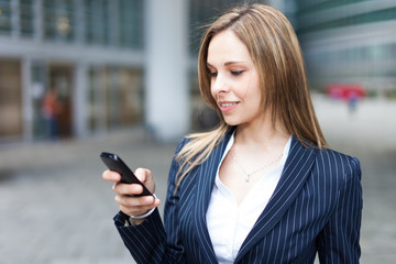 Portrait of a young smiling woman using her mobile phone