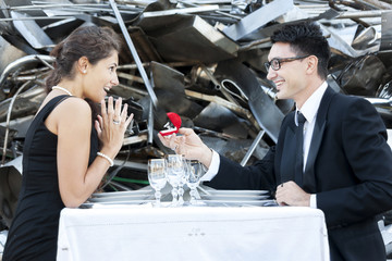 young adult gives an engagement ring at dinner