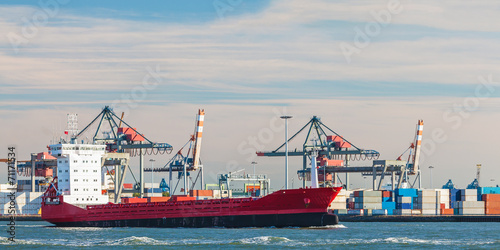 Container ship passing cranes in Rotterdam harbor - 71171534