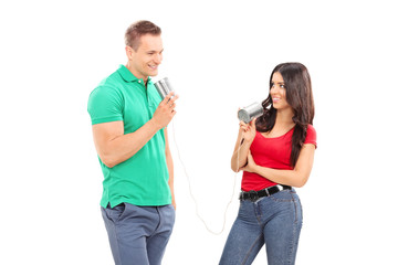 Young couple talking through a tin can phone