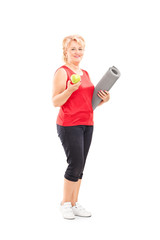 Mature female holding apple and an exercising mat