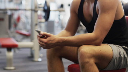 young man with smartphone computer in gym