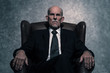 canvas print picture - In leather chair sitting senior businessman with gray beard wear