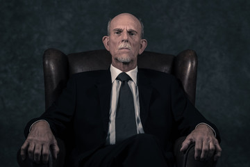 In leather chair sitting senior businessman with gray beard wear