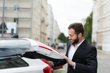 mann schließt kofferraum seines autos