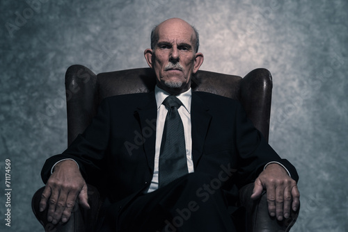 canvas print picture In leather chair sitting senior businessman with gray beard wear