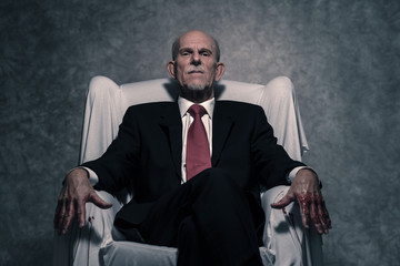 Bad businessman with bloody hands sitting in white chair. Gray b