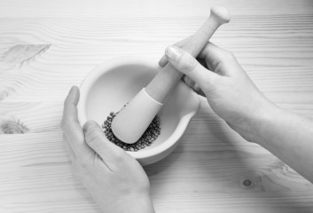 Two hands holding a pestle and mortar with whole coriander seeds