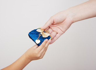 hands of mother gives the purse to her little daughter