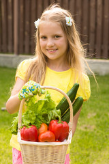 young girl holding basket of vegetables and looking at camera