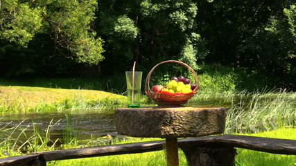 Basket with grape and peach fruit and glass with champagne cider