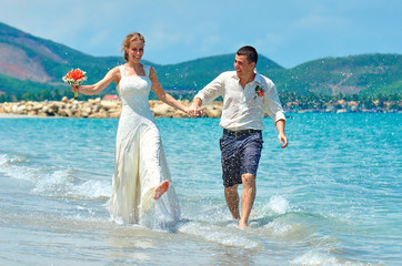 Happy Bride and groom running on a beautiful tropical beach
