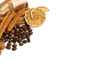 Coffee beans, cinnamon, lemon and sweets over white