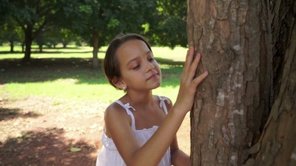 9of18 Happy school girl hugging tree in park, ecology