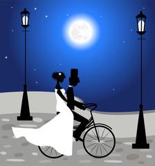 coppia di sposi in bicicletta sotto la luna