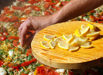 Cook puts lemon slices in the paella with seafood and peas