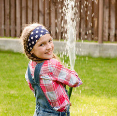 Happy cute little girl pouring water from a hose