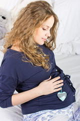 Beautiful pregnant blond woman with a big belly at home