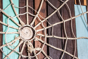 Spider web made of rope on the wood wall