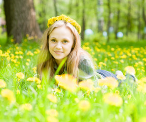 portrait beautiful girl with a wreath of dandelions lying on the