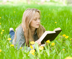 Pretty young woman lying on grass with dandelions and reading a