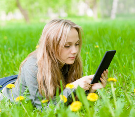 girl lying on grass with tablet computer
