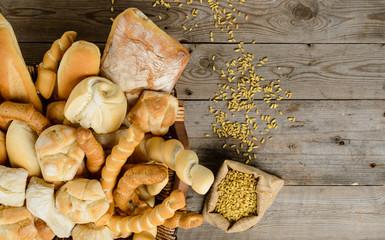 Vari tipi di pane e chicchi su piano di legno
