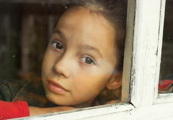 sad little girl looking through an old window
