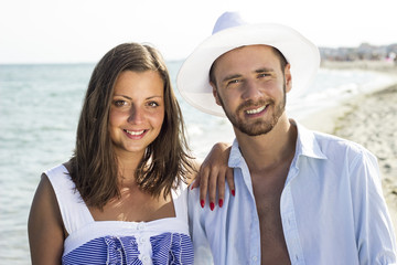 Smiling young couple portrait at beautiful summer beach
