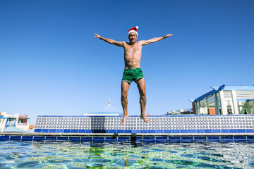 A man in a Santa Claus Cap jumps into a pool at a tropical resor