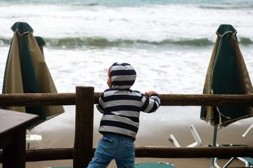 Ребенок наблюдает за непогодой на море