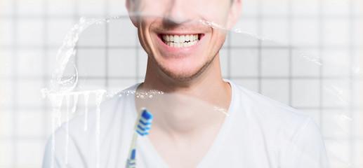 Junger Mann steht mit frisch geputzten zähnen vorm spiegel