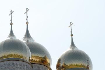 Golden cupola and christian cross on church against blue sky